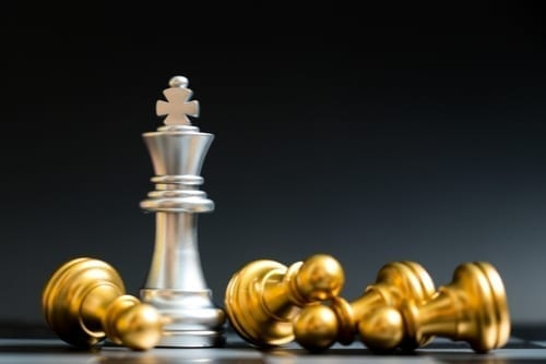 silver queen chess piece surrounded by fallen gold pawn pieces