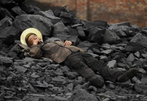 A labourer smokes while taking a rest at a cinder dump site in Changzhi